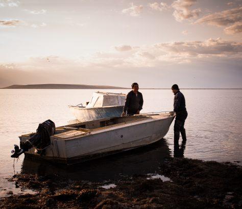Zwei Fischer fahren in die Abenddämmerung am Aralsee