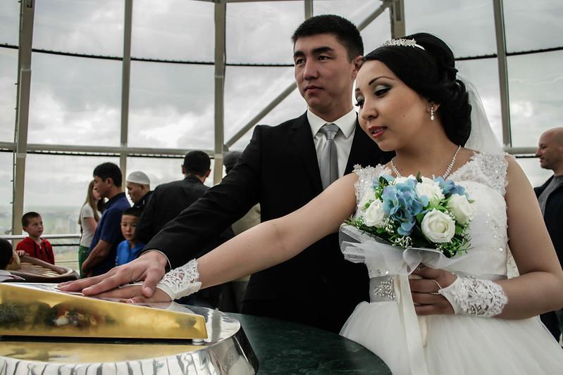 Ein Ehepaar legt im Baiterek-Turm in Nursultan die Hände in den goldenen Handabdruck des Ersten Präsidenten Kasachstans Nursultan Nazarbaev