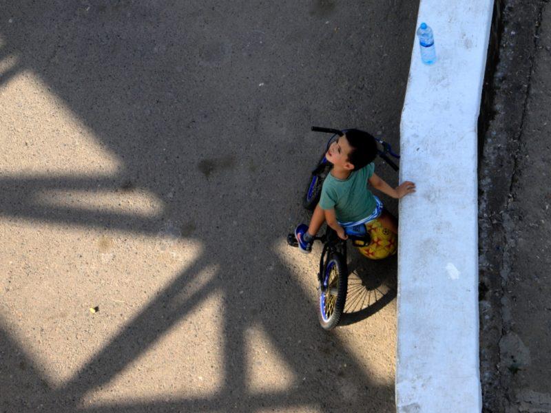 Straßenszene in Taschkent: Ein Junge blinzelt in die Sonne.