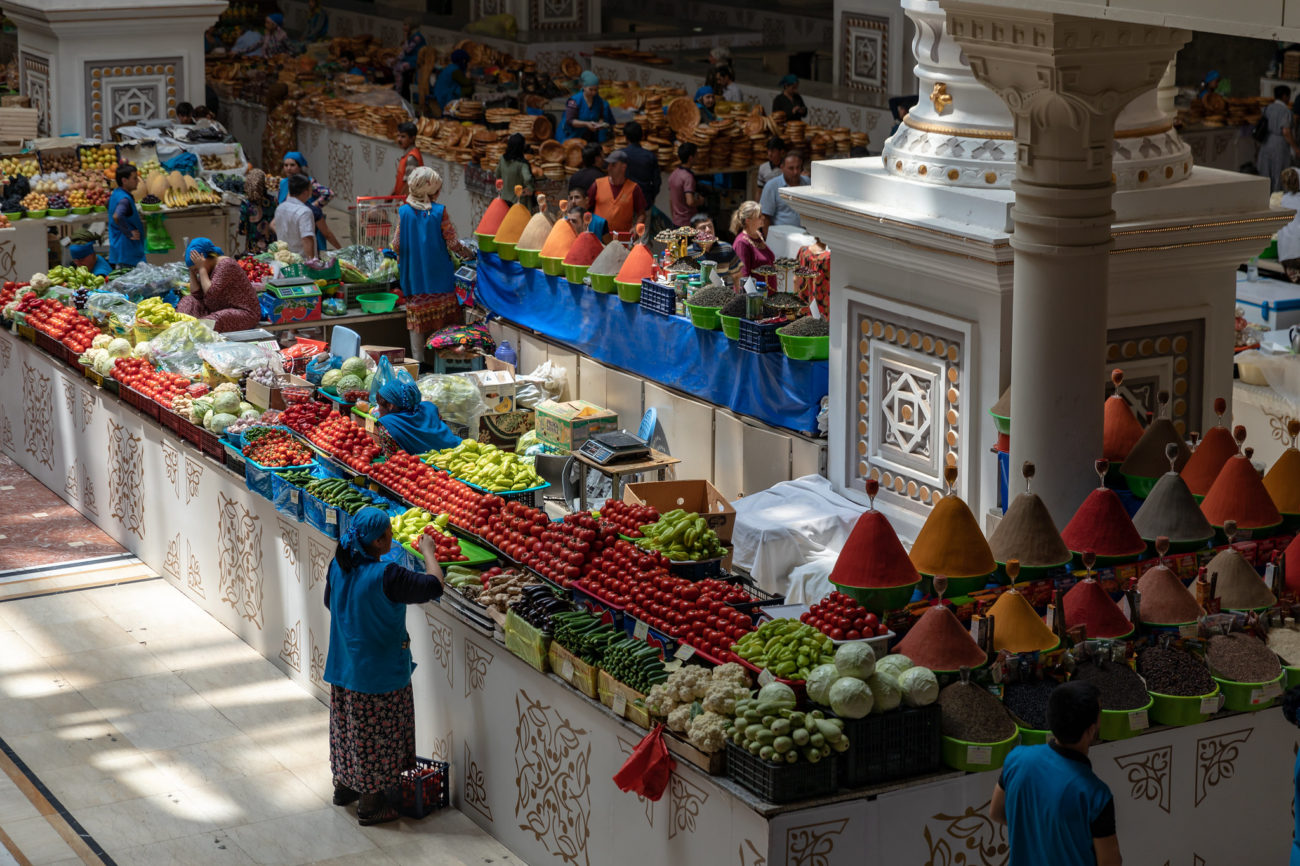 A woman is standing in front of a stall full of fruits at a bazar in Tajikistan