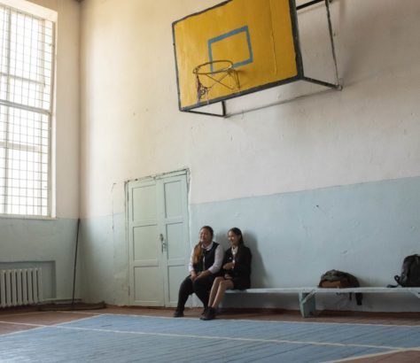 Two girls sit in a sports hall in Kyrgyzstan