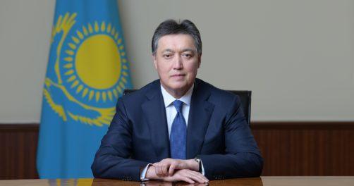 Aqar Mamin, prime minister of Kazakhstan, sitting in front of the flag of Kazakhstan