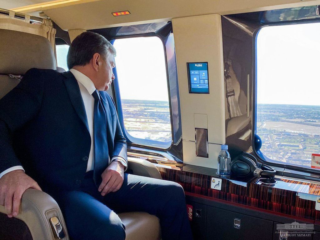 Picture of the president of Uzbekistan sitting on a plane and looking out the window