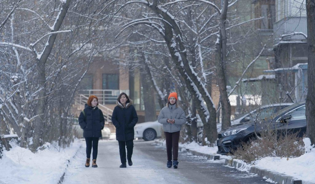Still from the film The Wife: three women walking in a city in winter