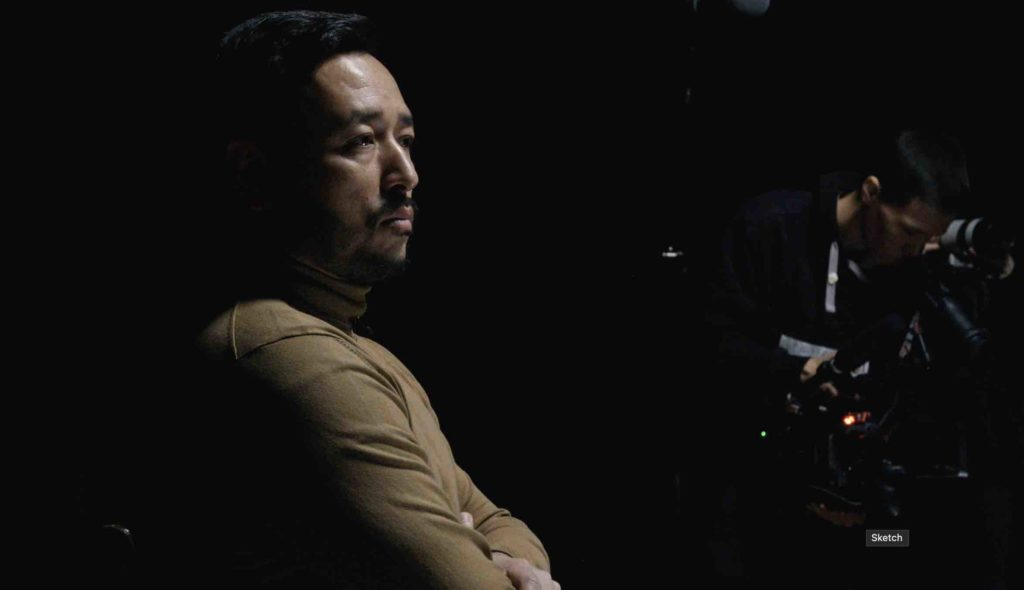 Still from the film The Wife: a man seen in profile against a dark background