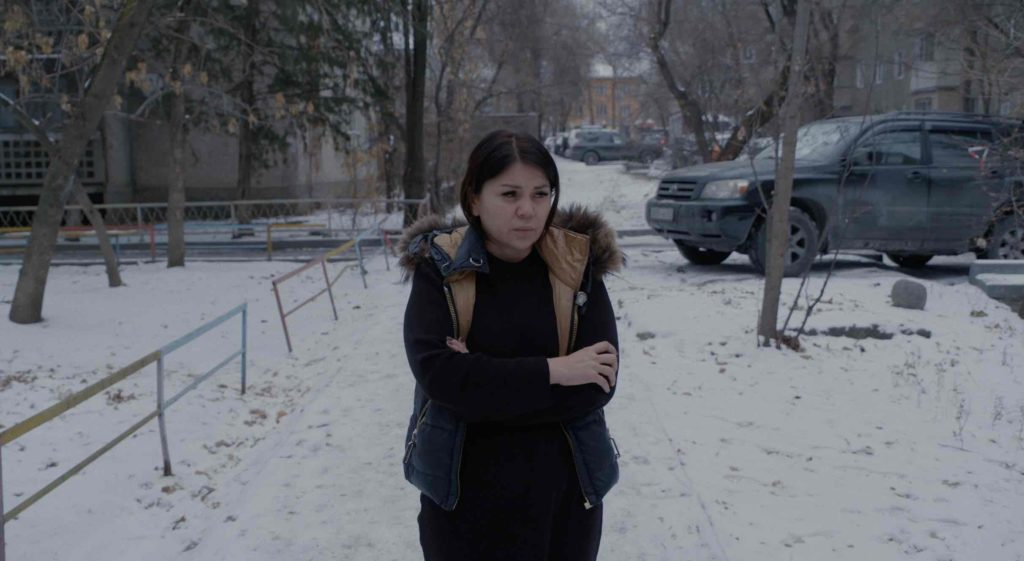Still from the film The Wife: a woman standing outside, surrounded by snow