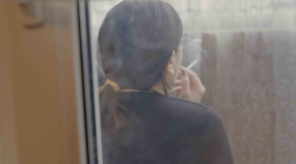 Still from the film The Wife: a woman smoking, seen from the back