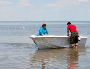 Two people pushing a small boat into the water in the Aral Sea region
