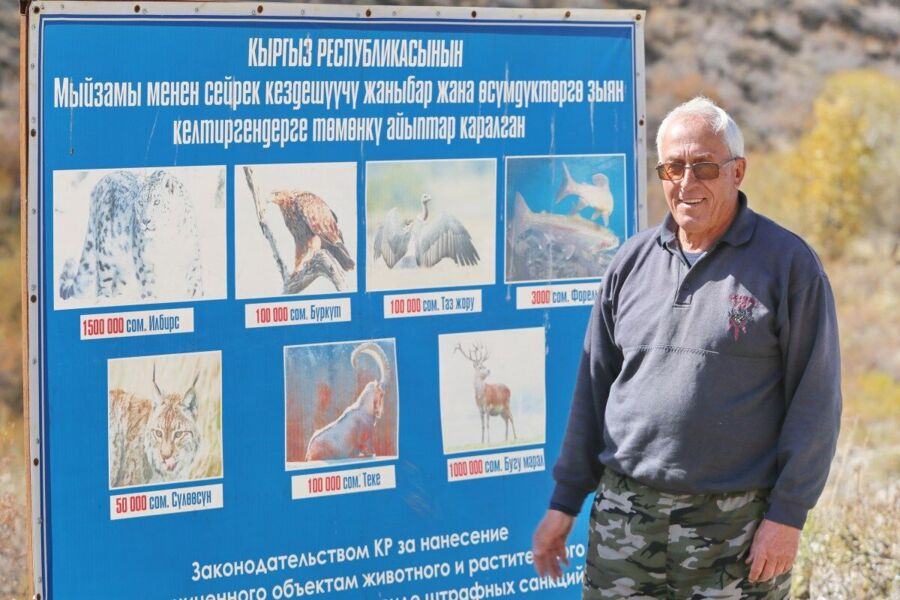 Vladimir Mazer stands by a sign explaining which animals are endangered