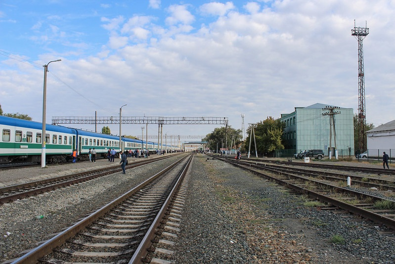Railroads at a station in Uzbekistan. There is a blue, white and green train on the left.