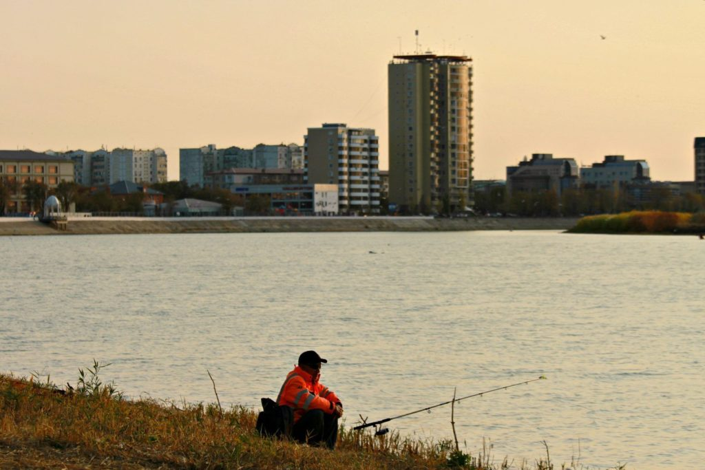 A man fishes in the Ural. He is wearing a bright orange jacket. In the background, a city,