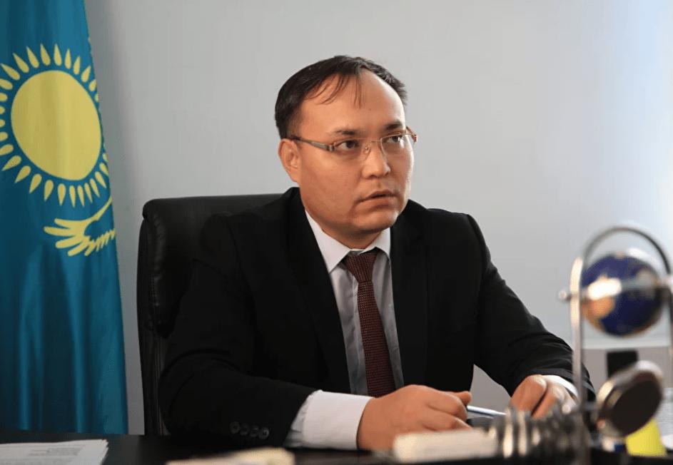 Galidolla Azidullin. Behind him, a Kazakh flag.