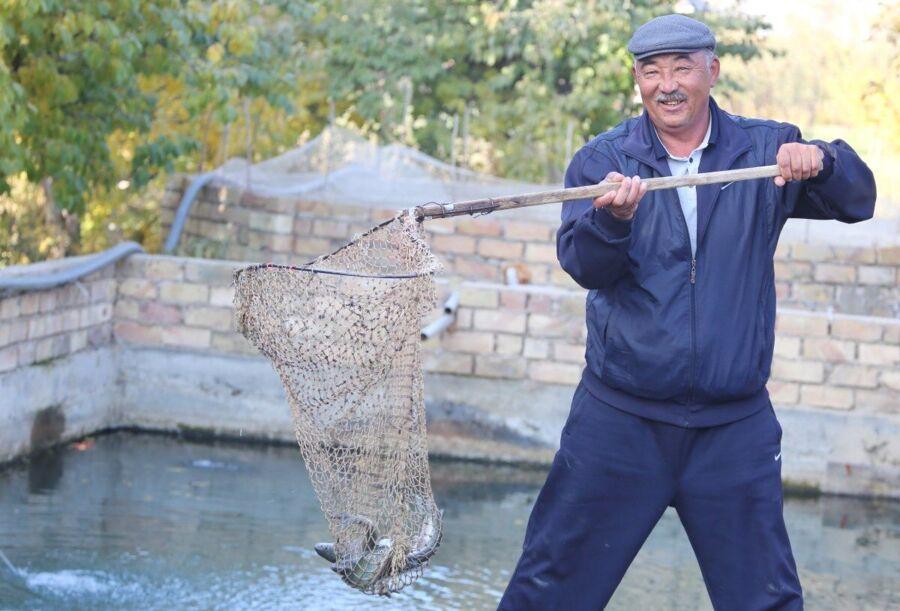 A man, Mysa Zhanchikulov, shows the fish he has caught