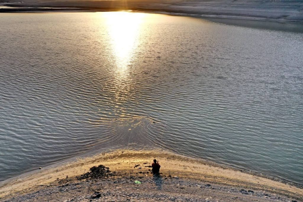 View of the Kirov reservoir. A figure is sitting by the water, fishing.