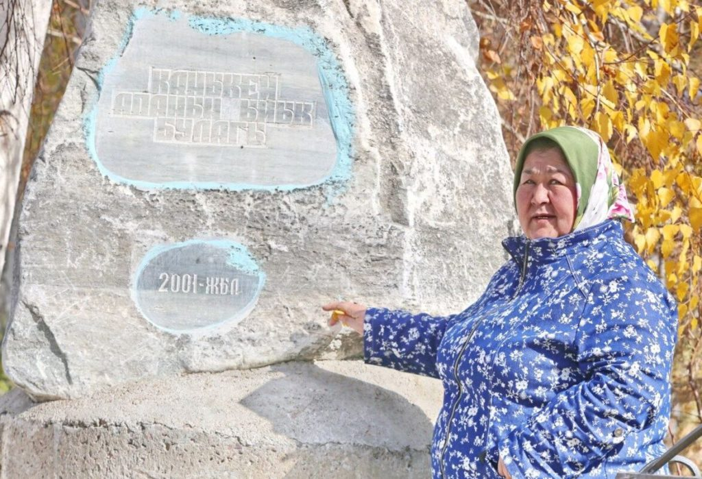 A woman wearing blue is standing by a rock with inscriptions in Kyrgyz commemorating a 2001 project