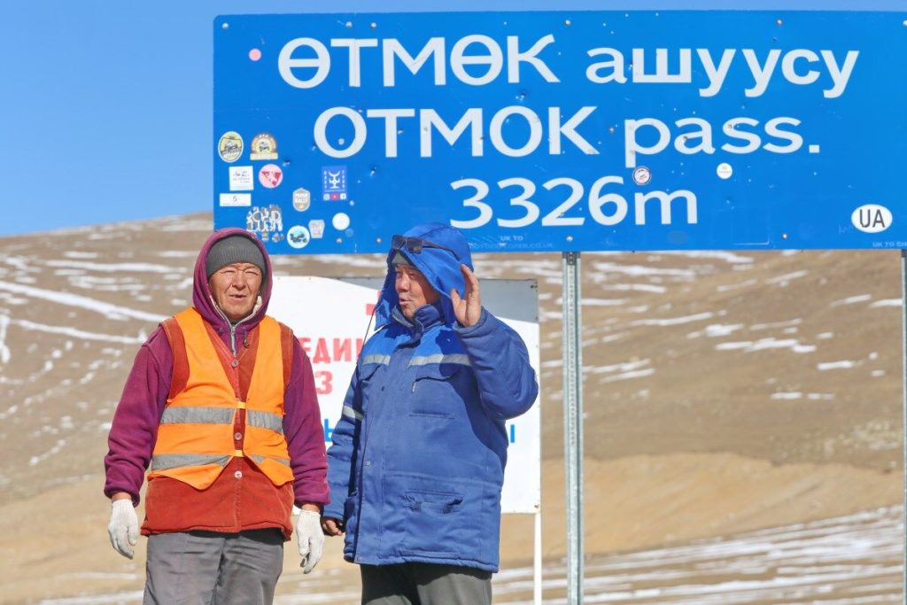"""Two people standing by a sign indicating """"Otmok pass, 3326m"""" in English and Kyrgyz. One is wearing blue, the other an orange hi-vis jacket."""