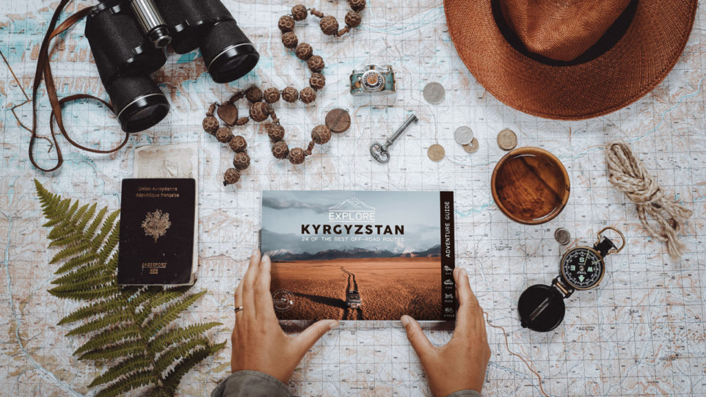 The book Explore Kyrgyzstan surrounded by a hat, a passport, binoculars, coins, a key, rope and other symbols of adventure travel