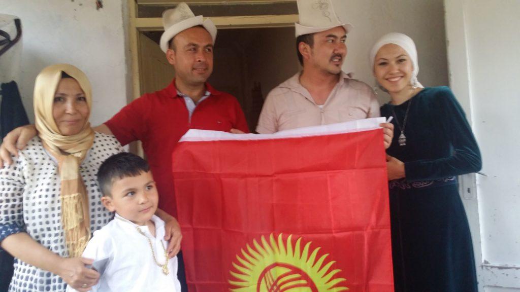 A Van Kyrgyz family pose for a photo with the Kyrgyz flag.