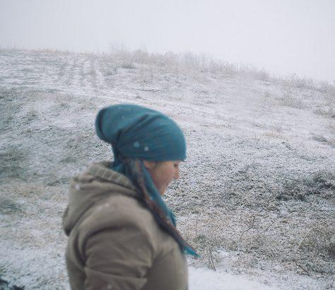 Une femme descendant du minibus dans l'hiver kirghiz, près de Mailuu-Suu au Kirghizstan