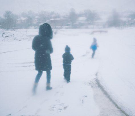 Une femme descend d'un minibus avec ses enfants au coeur de l'hiver kirghize,