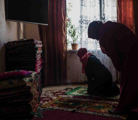 Akylay, une mère veuve de 45 ans membre de l'organisation Mutakalim, prie chez elle avec sa fille.